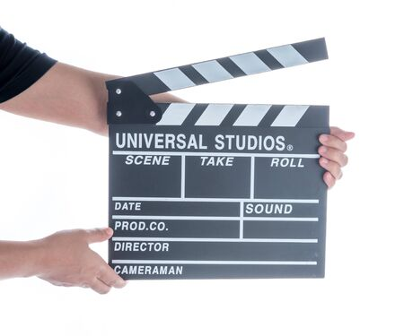 Woman holding movie production clapper board isolated on a white background