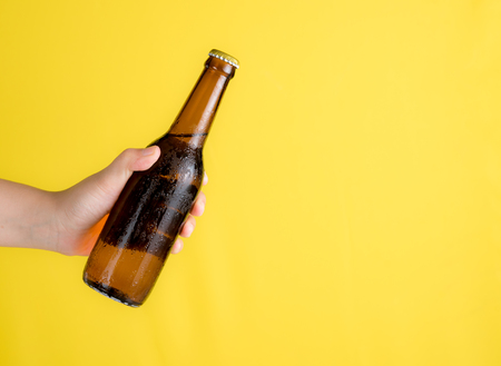 Hand holding beer bottle with text space against yellow background