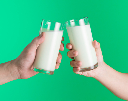Two hands holding glass of milk on green background,Clinking glasses of milk
