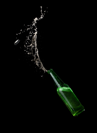 Green beer bottle opening with exploding and splashing on dark background