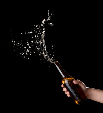 Gold beer bottle opening with exploding and splashing on dark background