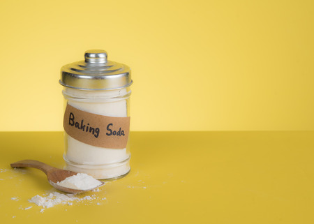 Jar of baking soda with text space against yellow background