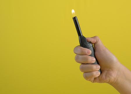 Hand with lighter igniting sparks against yellow background,text space Foto de archivo