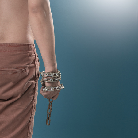 Terrorists Prisoner with chained hand against blue background,criminal concept