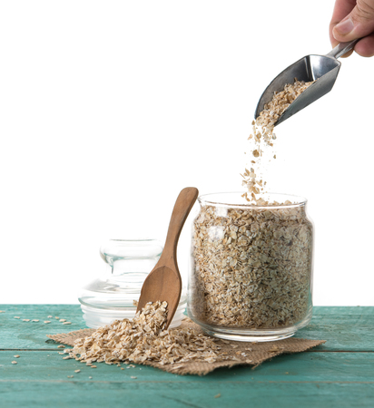 Oatmeal or oat flakes in jar on wood table against white background
