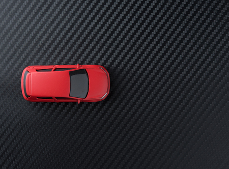 Red miniature car on carbon kevlar,top view