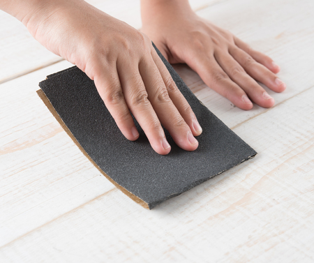 Sanding and smoothing wood with black sandpaper