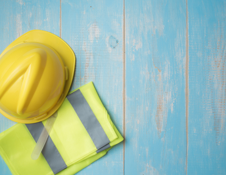 Safety helmet and yellow shirt on wood background,top view for copy space
