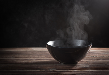 Steam of hot soup with smoke in ceramic bowl against black cement wall