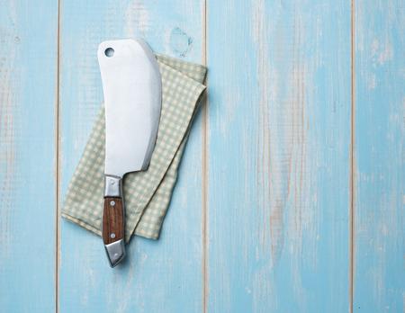 Old butcher knife on blue wooden background