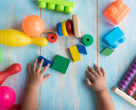 Child's hands playing with children's toys on the blue table background,Learning and education concept.