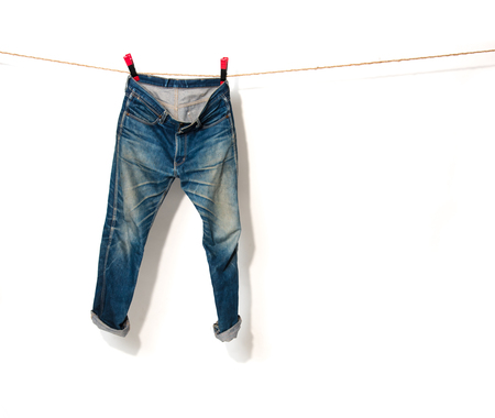 Blue Jeans hanging on a rope clothesline,white background