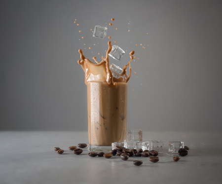 Iced coffee splash with ice cubes and beans against grey concrete Stok Fotoğraf