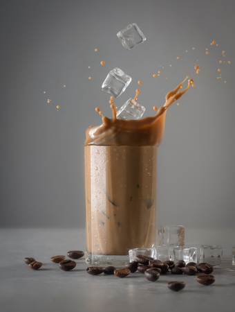 Iced coffee splash with ice cubes and beans against grey concrete Banco de Imagens
