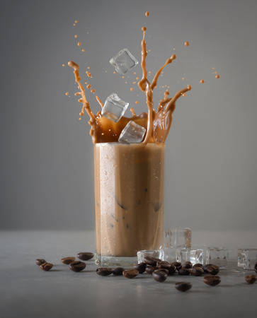 Iced coffee splash with ice cubes and beans against grey concrete Banque d'images