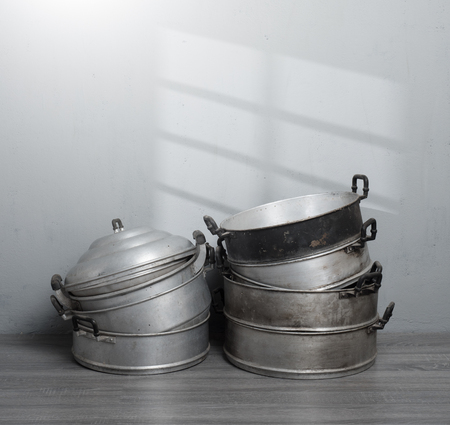 Old stainless steel steamer pot against gray wall background,original style Thai cooking