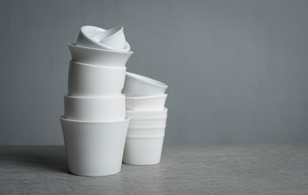 Stack of cups on table against gray background
