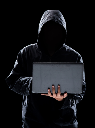 Hacker with hidden face in a hoodie using a laptop on black background Banco de Imagens