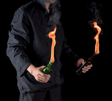 Molotov cocktail bottle with fire in the hand on a black background.