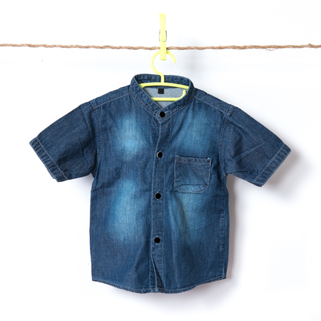 Baby jean shirt hanging on the clothesline against white background Imagens