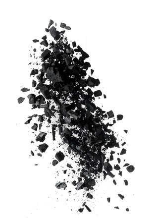 Activated charcoal powder splash or explosion flying in the air isolated on white background