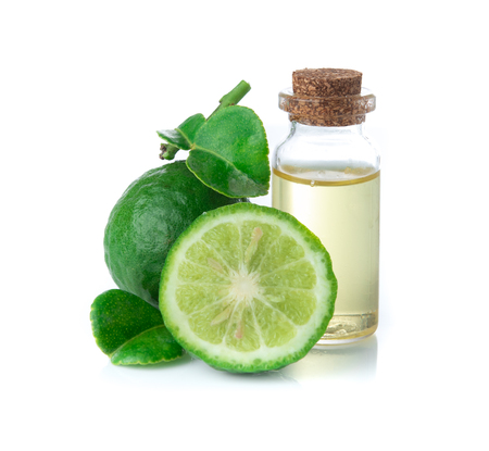 Fresh bergamot fruit and bergamot essential oil in glass bottle on white background