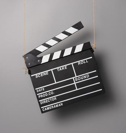 Batacchio per film Foto scattata appesa a corde, sfondo grigio Archivio Fotografico