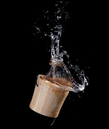 Wooden bucket with water splash or explosion flying in the air isolated on black Imagens