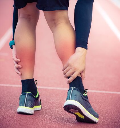 Male runner calf leg injury and pain on running track,Injury from workout concept Stock Photo - 128004665