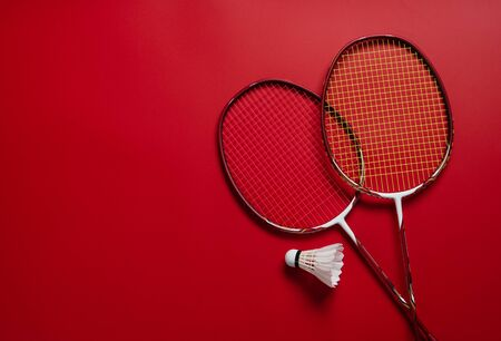 Shuttlecocks and badminton racket on red background,top view Stock Photo