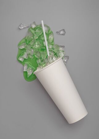 Close up of a paper glass of green sparkling water with ice cubes spilled on grey background,top view Banque d'images - 131771286