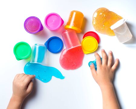 Childs hands playing with colorful slime on white background,top view 写真素材