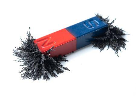 Imán de barra rojo y azul que atrae polvo de hierro sobre fondo blanco. Foto de archivo