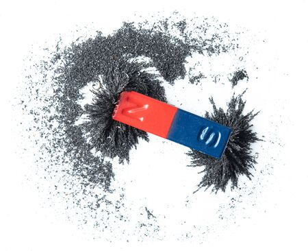 Red and blue bar magnet attracting iron powder on white background