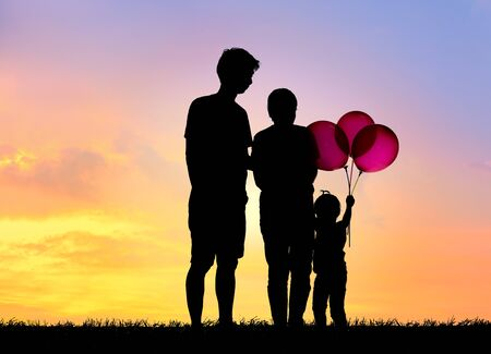 Famille silhouette, père, mère et enfants tenant des balles contre le coucher du soleil.