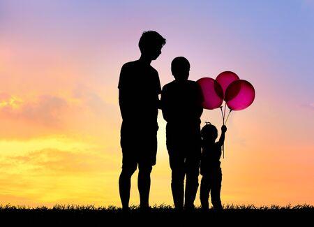 Profili la famiglia, il padre, la madre e i bambini che tengono le palle contro il tramonto.