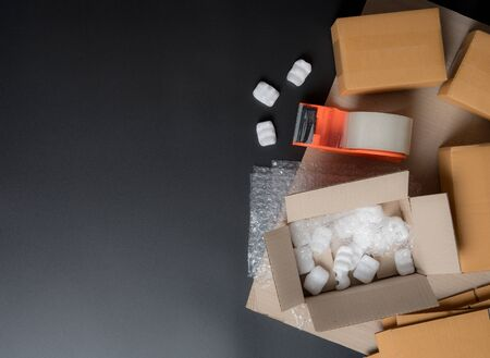 Packing accessories on dark background,Foam cushion,Shockproof plastic wrap,Cardboard boxes with tape,Packing, shipping concept