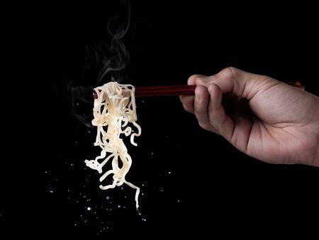 Hand holding bamboo chopsticks to eat instant noodles with steam and smoke isolated on black