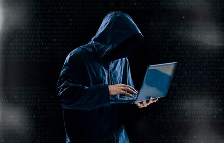 Internet crime concept,Hooded hacker using laptop in dark room