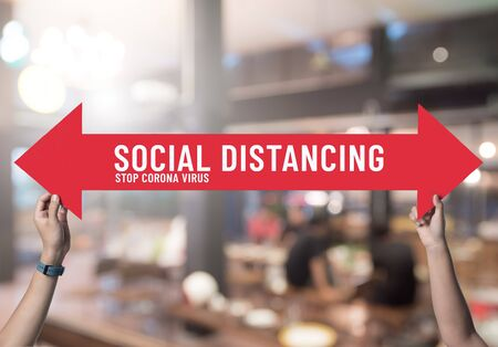 Social distancing,holding sign with message about social distancing ,Space between people to avoid spreading COVID-19 Virus in restaurant,New normal Archivio Fotografico