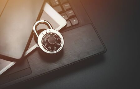 Cyber safety concept,Combination Lock with laptop computer,notepad and smartphone,Protection of private personal data. A person using internet