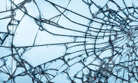 Broken glass texture close up on blue background Stockfoto