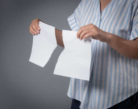 Woman holding torn sheet of paper against on gray background