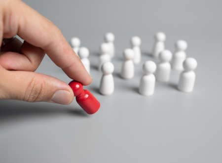 Hand chooses a icon people standing out from the crowd,Successful team leader Standard-Bild