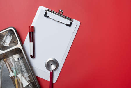 Healthcare concept : Stethoscope, tube of blood and blank medical clipboard