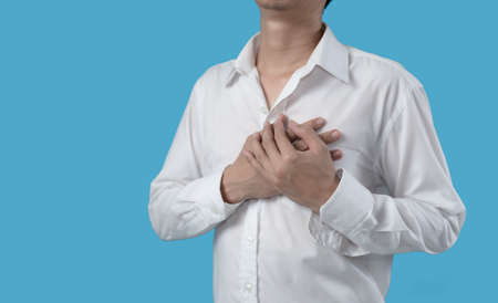 Man holding hands on chest suffering from heart attack on blue background Banque d'images