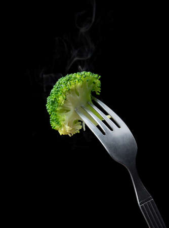 Fork with boiled broccoli on black background