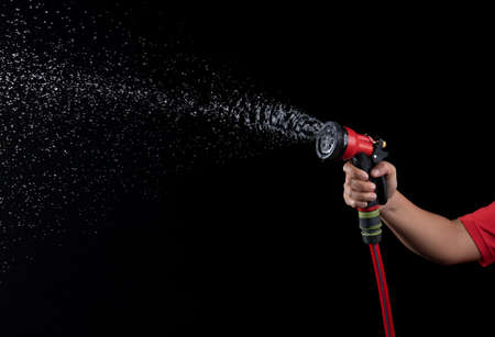 Hand hold a gun watering hose with water splash against on black background,spraying hose nozzle Banque d'images