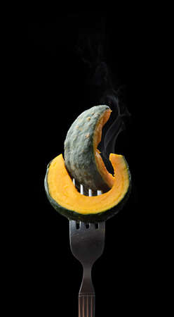 Fork with slices of boiled fresh pumpkin on black background