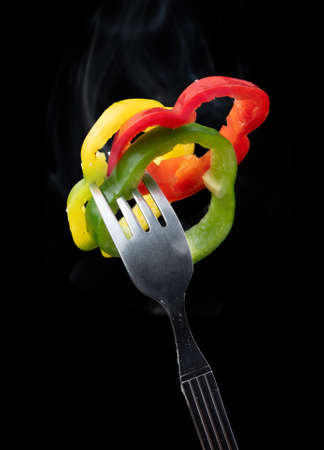 Fork with slice peppers on black background Banque d'images